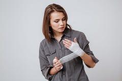Kranke traurige junge Frau mit dem Gips an Hand lizenzfreies stockfoto