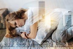 Kranke weibliche Person, die auf ihrem Bett liegt Stockfotos
