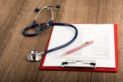 Krankengeschichte mit Stethoskop und Stift Stockfotografie