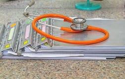 Krankengeschichteordner mit Stethoskop auf Marmorsteinschreibtisch Stockfotografie