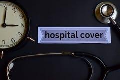 Krankenhaus-Abdeckung auf dem Druckpapier mit Gesundheitswesen-Konzept-Inspiration Wecker, schwarzes Stethoskop lizenzfreie stockfotos