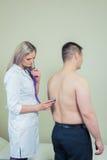Krankenhaus: Arzt-Checks Patient With-Stethoskop Lizenzfreie Stockbilder
