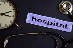 Krankenhaus auf dem Druckpapier mit Gesundheitswesen-Konzept-Inspiration Wecker, schwarzes Stethoskop lizenzfreie stockbilder