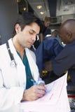 Krankenhausdoktor, der Anmerkungssanitäter nimmt Stockbild