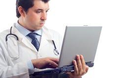 Krankenhausdoktor, der an einem Laptop arbeitet Stockfotos