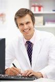 Krankenhausdoktor am Schreibtisch Stockfoto