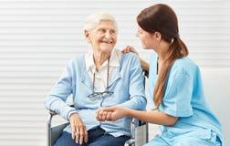 Krankenpflegefrau, die einen älteren Bürger unterstützt stockfotos