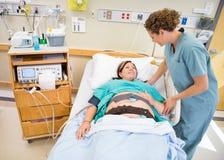 Krankenschwester-Communicating With Pregnant-Patient, der herein liegt lizenzfreie stockfotografie