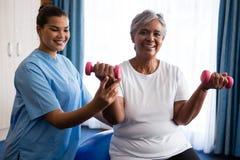 Krankenschwester, die ältere Frau in anhebenden Dummköpfen unterstützt stockfotografie