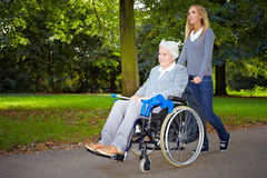 Krankenschwester, die ältere Frau antreibt Stockbild