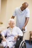 Krankenschwester, die ältere Frau im Rollstuhl drückt Stockbild