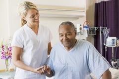 Krankenschwester, die älterem Mann hilft zu gehen Stockbild