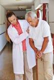 Krankenschwester, die älterem Mann mit Stock hilft Lizenzfreie Stockbilder