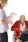 Krankenschwester, die älteren Patienten überprüft Stockbild