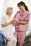 Krankenschwester, die älterer Frau hilft zu gehen Stockfotos