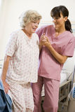 Krankenschwester, die älterer Frau hilft zu gehen Stockfoto