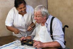 Krankenschwester, die altem Mann hilft Stockfotos