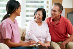 Krankenschwester, die Anmerkungen während des Hauptbesuchs mit älteren Paaren macht Lizenzfreie Stockfotos