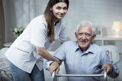 Krankenschwester, die arbeitsunfähigem älterem Mann hilft Lizenzfreie Stockfotografie