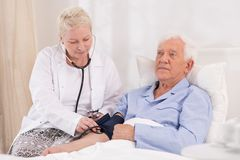 Krankenschwester, die Blutdruck nimmt Stockbild