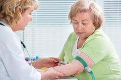 Krankenschwester, die Blutprobe entnimmt Lizenzfreie Stockfotos