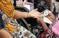 Krankenschwester, die Blutzuckerspiegel der Frau überprüft Stockbild