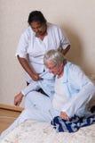Krankenschwester, die dem älteren Mann erhält angekleidet hilft lizenzfreies stockfoto