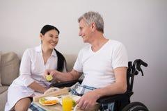 Krankenschwester, die dem Patienten im Rollstuhl Lebensmittel holt lizenzfreie stockfotografie