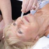 Krankenschwester, die dem Patienten Nasentropfen gibt Stockfotos