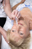 Krankenschwester, die dem Patienten Nasentropfen gibt Lizenzfreie Stockfotos