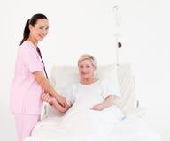 Krankenschwester, die den Impuls eines Patienten misst Lizenzfreie Stockfotos