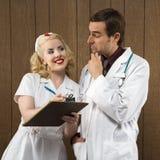 Krankenschwester, die am Doktor lächelt. Lizenzfreies Stockbild