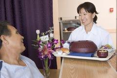 Krankenschwester, die einem Patienten eine Mahlzeit in seinem Bett dient Stockfotos