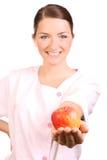 Krankenschwester, die einen Apfel anbietet Stockfoto