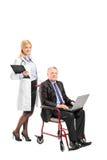 Krankenschwester, die einen Geschäftsmann im Rollstuhl drückt Stockfotografie