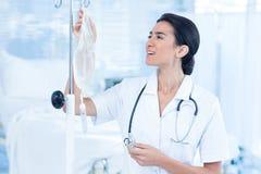 Krankenschwester, die einen intravenösen Tropfenfänger anschließt Stockfoto