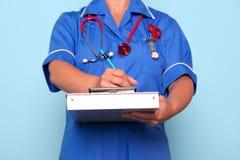Krankenschwester, die einen medizinischen Report schreibt Stockbilder