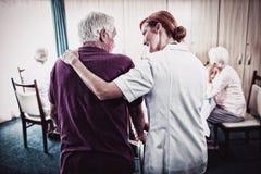 Krankenschwester, die einen Senior verwendet einen Wanderer unterstützt stockbilder