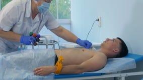 Krankenschwester, die Elektrokardiographie auf einem männlichen Patienten durchführt Lizenzfreie Stockfotografie