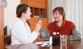 Krankenschwester, die für ältere Frau sich interessiert Stockfotos