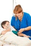 Krankenschwester, die für krankes Kind sich interessiert Lizenzfreie Stockfotografie