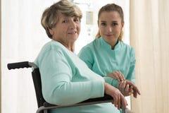 Krankenschwester, die für ältere Dame sich interessiert Lizenzfreies Stockfoto
