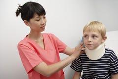 Krankenschwester, die Halsklammer anwendet stockfotos