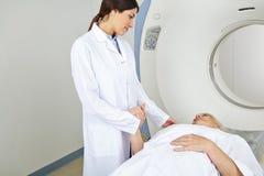 Krankenschwester, die Hand des Patienten an MRT hält Stockfoto
