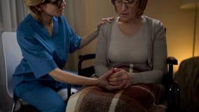 Krankenschwester, die herzlich mit alter Frau im Rollstuhl, sie stützend, älteres Haus spricht lizenzfreie stockfotografie