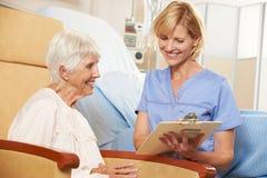 Krankenschwester, die Kenntnisse vom älteren weiblichen Patienten gesetzt im Stuhl nimmt Stockbild