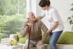 Krankenschwester, die älterem Mann hilft Stockfotografie
