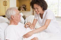 Krankenschwester, die älterem Mann hilft Lizenzfreies Stockbild