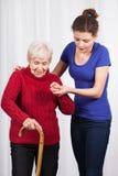 Krankenschwester, die älterer Dame hilft zu gehen Stockfotos