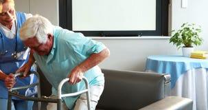 Krankenschwester, die Mann im Ruhestand mit Wanderer hilft stock footage